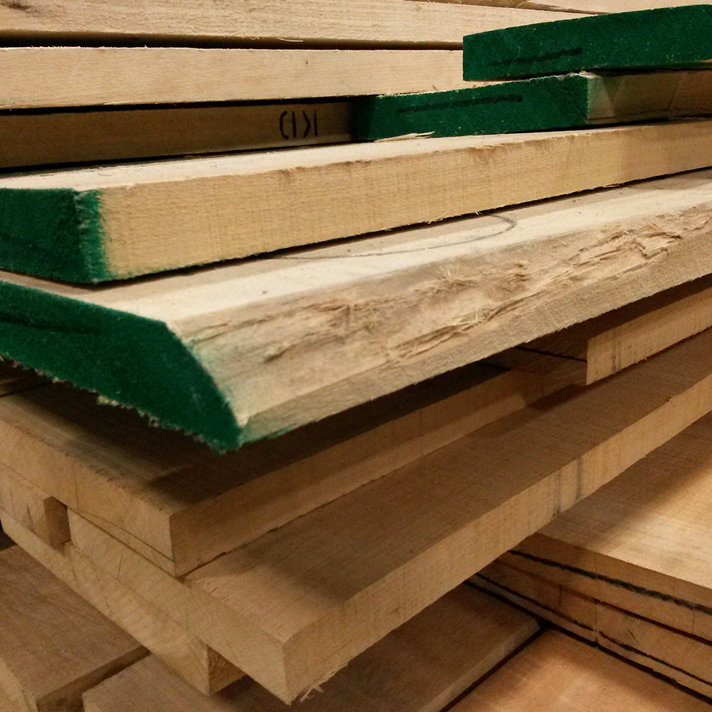 Large stack of rough cut lumber in various sizes and thicknesses